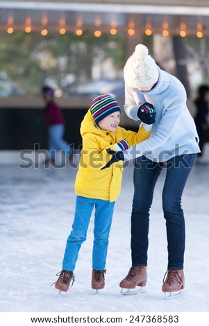 happy mother and her little son having fun ice skating together at winter - stock photo
