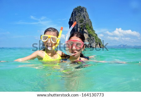 Happy mother and kid snorkeling in tropical sea, family beach vacation  - stock photo
