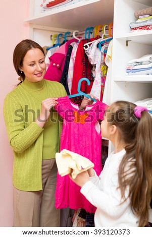 Happy mother and little child staying near wardrobe with dresses on hangers. - stock photo