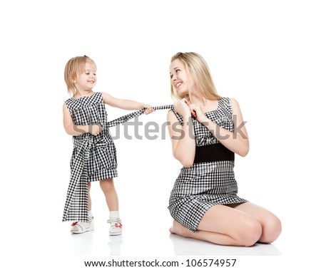happy mother and little daughter hold drag fabric cloth from dress smile isolated over white background, concept of family love 2 year cute girl child play fashion designer with mom - stock photo
