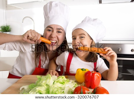 happy mother and little daughter in apron and cook hat preparing salad and eating carrots together having fun at home kitchen smiling playful in healthy nutrition and education concept - stock photo