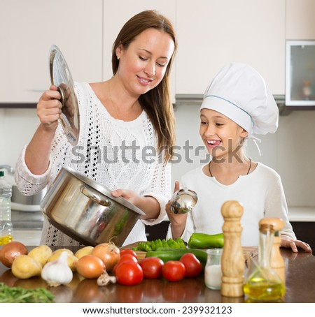 Happy mother and little daughter preparing soup together - stock photo