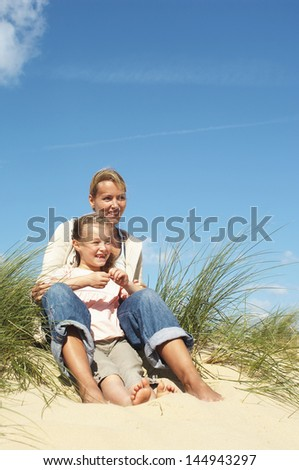 Happy mother and little daughter sitting on sand at beach - stock photo