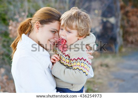 Happy mother and little son, cute kid boy in park or forest, outdoors. Hugging and having fun together at sunset. Beautiful family, carefree childhood and motherlove concept. - stock photo