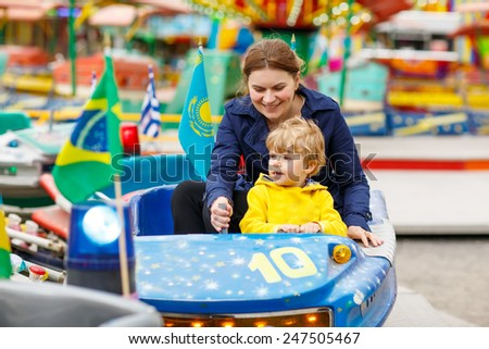 Happy mother and little son riding on a merry-go-round carousel together, smiling and having fun at a fair or amusement park. Active family leisure with kids. - stock photo