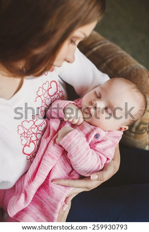 Happy mother and sleeping baby. caring mother kissing little fingers of her cute sleeping baby girl, happy family concept. Young mother is holding her cute newborn baby girl - stock photo
