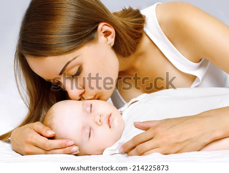 Happy mother and sleeping baby in the bed - stock photo