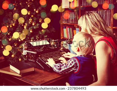 Happy mother and small boy typing letter to Santa on old typewriter before Christmas - stock photo