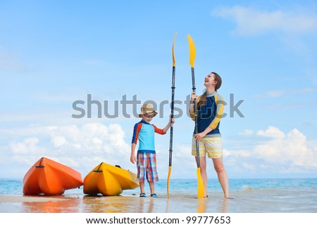 Happy mother and son at beach after kayaking - stock photo