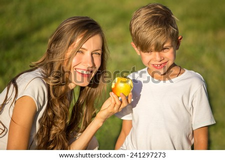 Happy mother and son eating apple. outdoor shot, daylight - stock photo