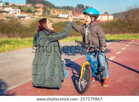 Happy mother and son giving five by the success in the learn to ride a bicycles in the city on a sunny winter day.  Family leisure outdoors concept. - stock photo