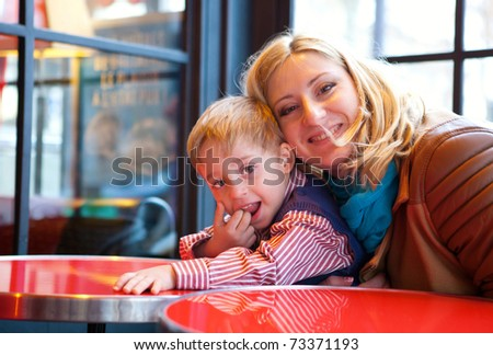 Happy mother and son in a Parisian cafe - stock photo