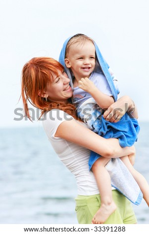 happy mother and son on beach - stock photo