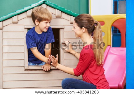 Happy mother and son playing a clapping game in nursery at home - stock photo