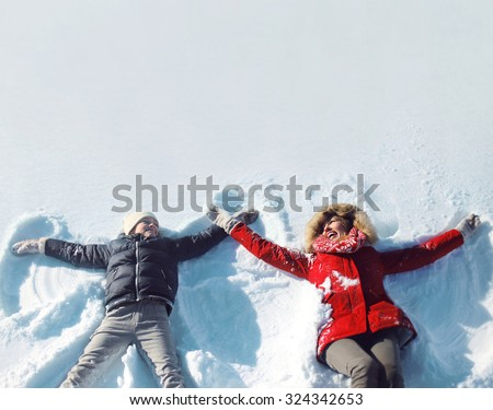 Happy mother and son playing and having fun together lying in the snow on a sunny winter day - stock photo