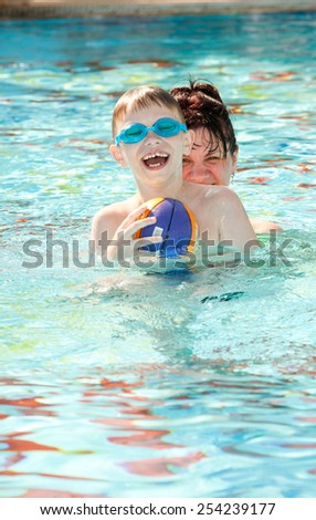 happy mother and son playing in the pool - stock photo