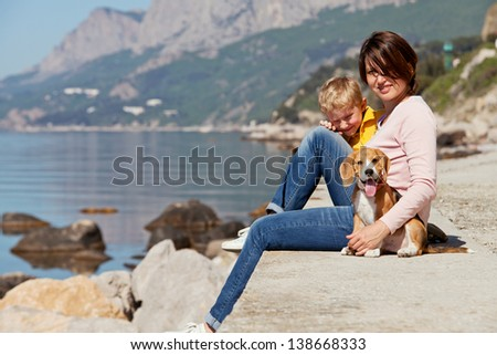 Happy mother and son sitting on the quay with beagle puppy - stock photo