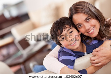 Happy mother and son smiling at home - stock photo