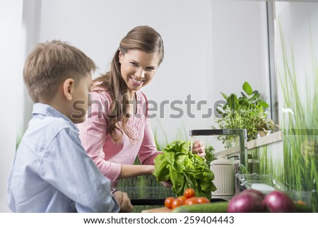 Happy mother and son washing vegetables in kitchen - stock photo