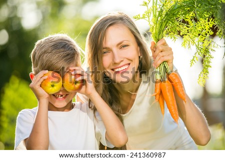 Happy mother and son with vegetables enjoy healthy eco organic food. focus on mother - stock photo