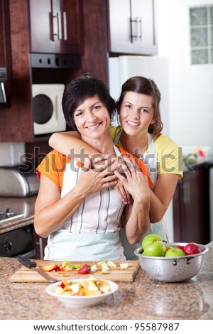 happy mother and teen daughter in kitchen - stock photo