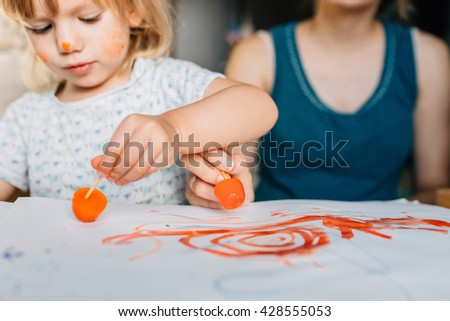 Happy mother and toddler girl painting with ice cubes and paints. They paint their faces and on the paper having fun. - stock photo