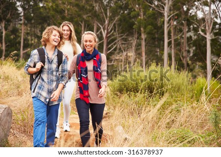 Happy mother and two kids walking in a forest - stock photo