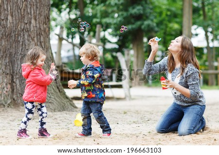 Happy mother and two little children playing together with soap bubbles on playground in summer - stock photo