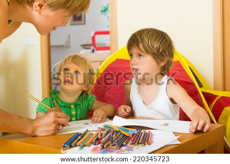 Happy mother and two little girls sketching on paper in home interior  - stock photo