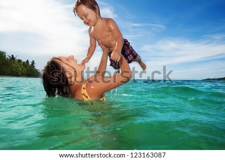 Happy mother and two years old baby swimming playing in the water in the see on their summer vacation - stock photo