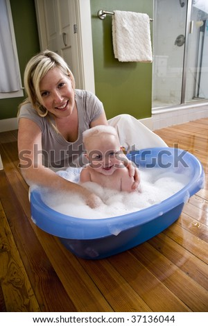 Happy mother bathing her cute 7 month old baby - stock photo