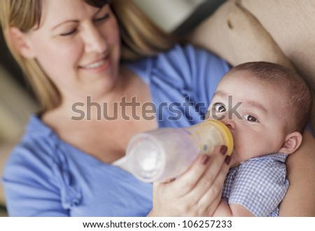 Happy Mother Bottle Feeding Her Very Content Son. - stock photo