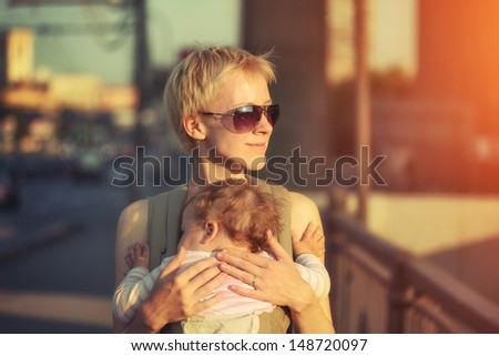 Happy mother carrying baby daughter child in sling on city street at sunset. - stock photo