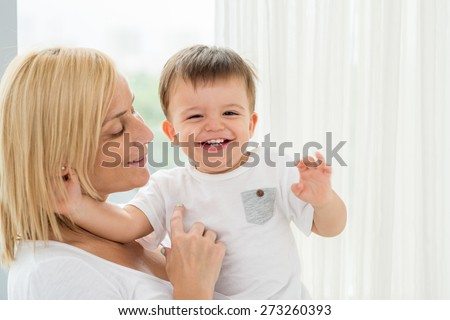 Happy mother carrying her cheerful giggling son - stock photo