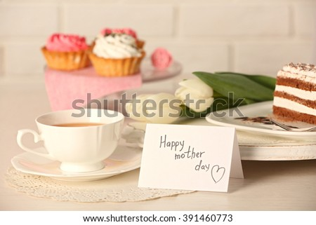 Happy mother day greeting with tulips, cup of tea and delicious cupcakes on wooden table closeup - stock photo