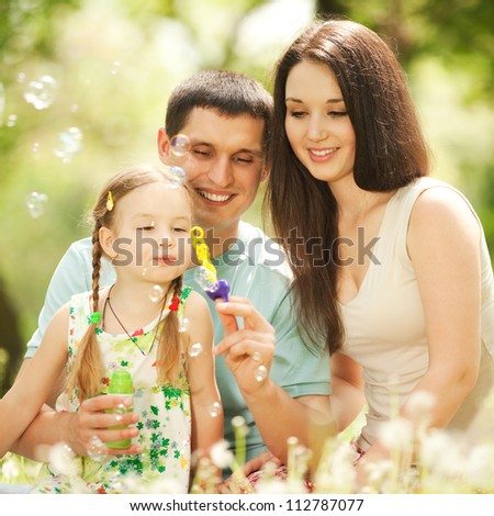 Happy mother, father and daughter blowing bubbles in the park - stock photo