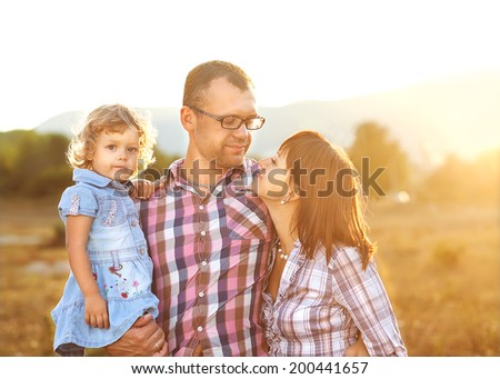 Happy mother, father and daughter in sunset - stock photo