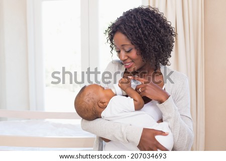 Happy mother feeding her baby boy his bottle at home in the bedroom - stock photo