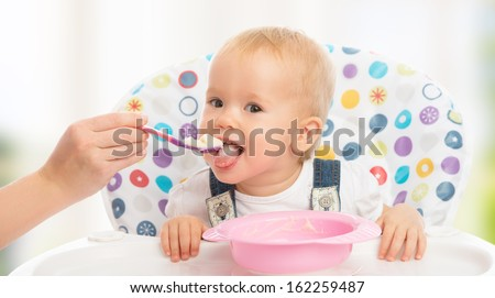 happy mother feeds funny baby from a spoon - stock photo