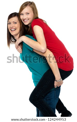 Happy mother giving piggy back ride to her daughter isolated on white background. - stock photo