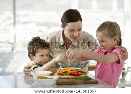 Happy mother helping children to prepare meal in kitchen - stock photo
