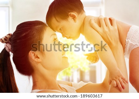 Happy  mother holding adorable child baby with sunrise background - stock photo