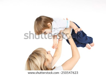 happy mother holding and lifting up her one year old baby boy over white  background - stock photo