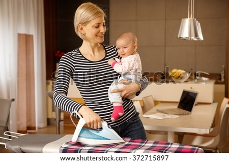 Happy mother holding baby in arm, ironing. - stock photo