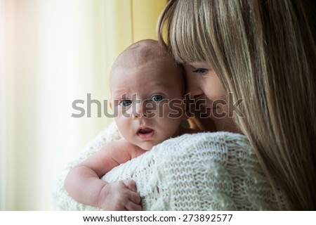 Happy mother holding her baby at home by the window - stock photo