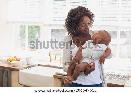 Happy mother holding her baby boy at home in the kitchen - stock photo
