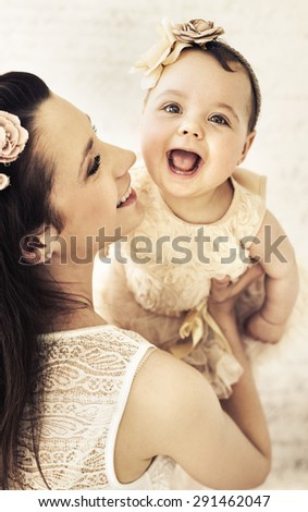 Happy mother holding her baby girl - stock photo