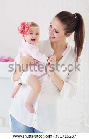 Happy mother holding her baby girl at home - stock photo