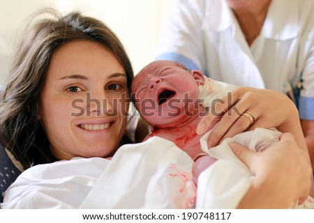 Happy mother holding her baby, seconds after she gave a birth, natural child birth - stock photo