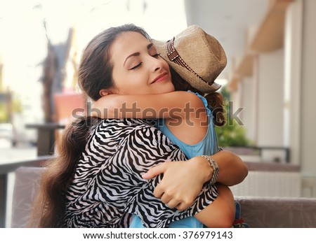 Happy mother hugging her daughter with love and natural emotion smiling with closed eyes - stock photo